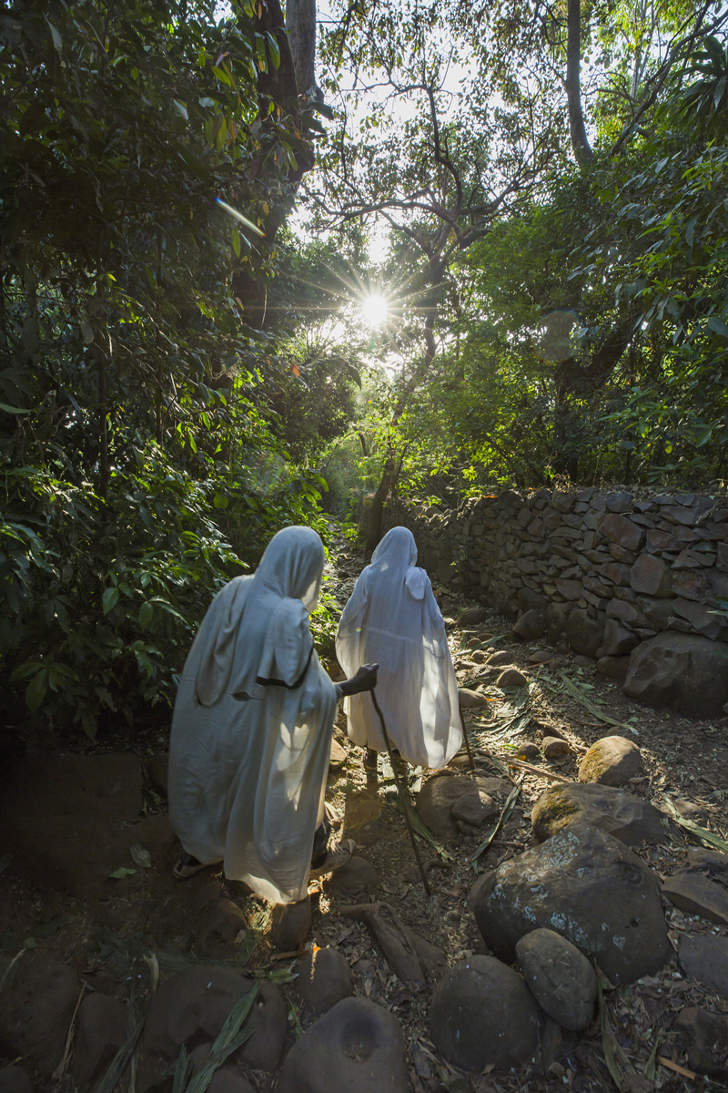 Two women walk towards Betre Mariam church