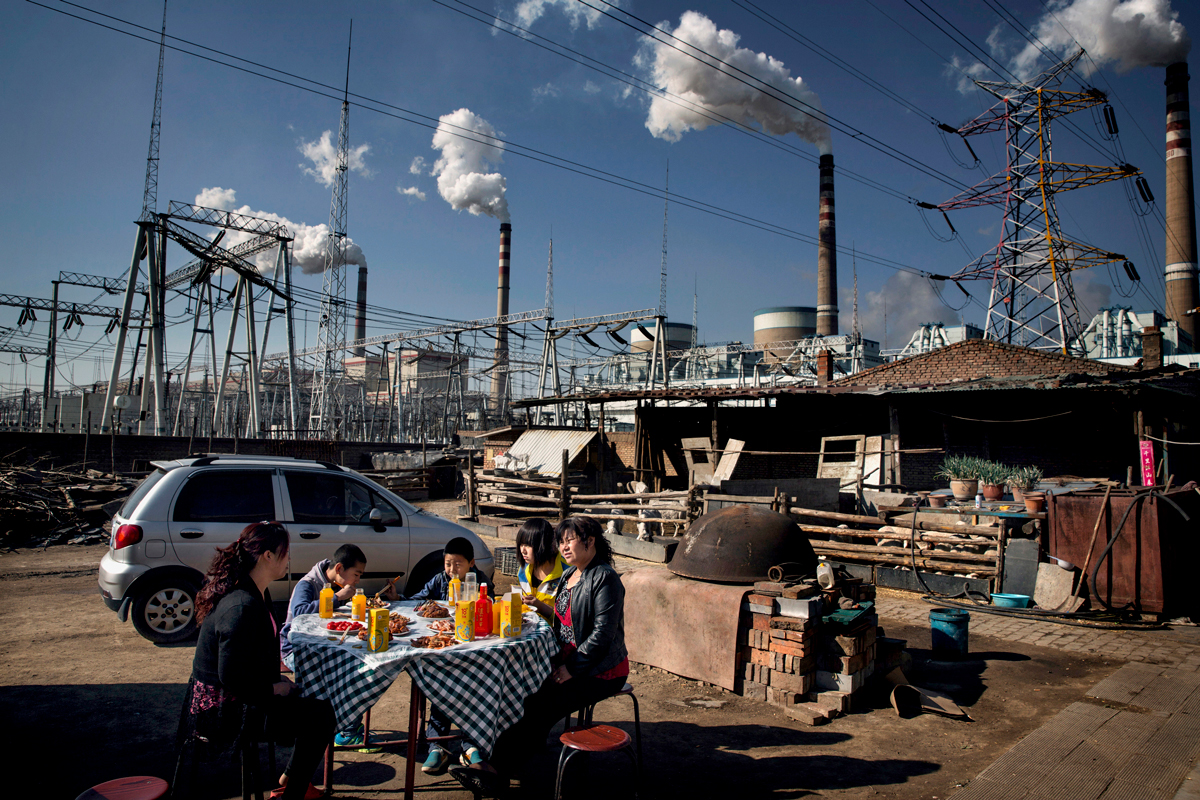A family eats a meal beneath the smoke stacks and pylons of the Datong No. 2 coal fired power plant.