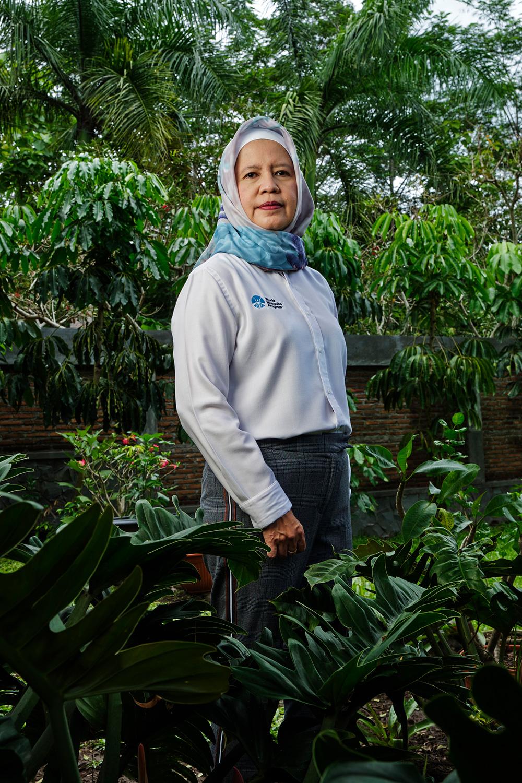 Adi Utarini photographed surrounded by tropical                vegetation.