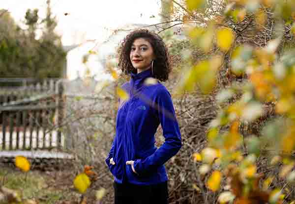 Chanda Prescod-Weinstein poses for a portrait in an Autumnal garden.