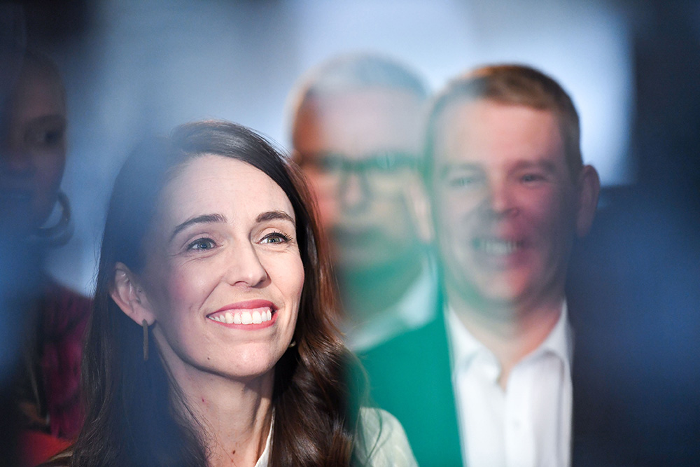 Jacinda Ardern smiling whist surrounded by her Labour                Party colleagues.