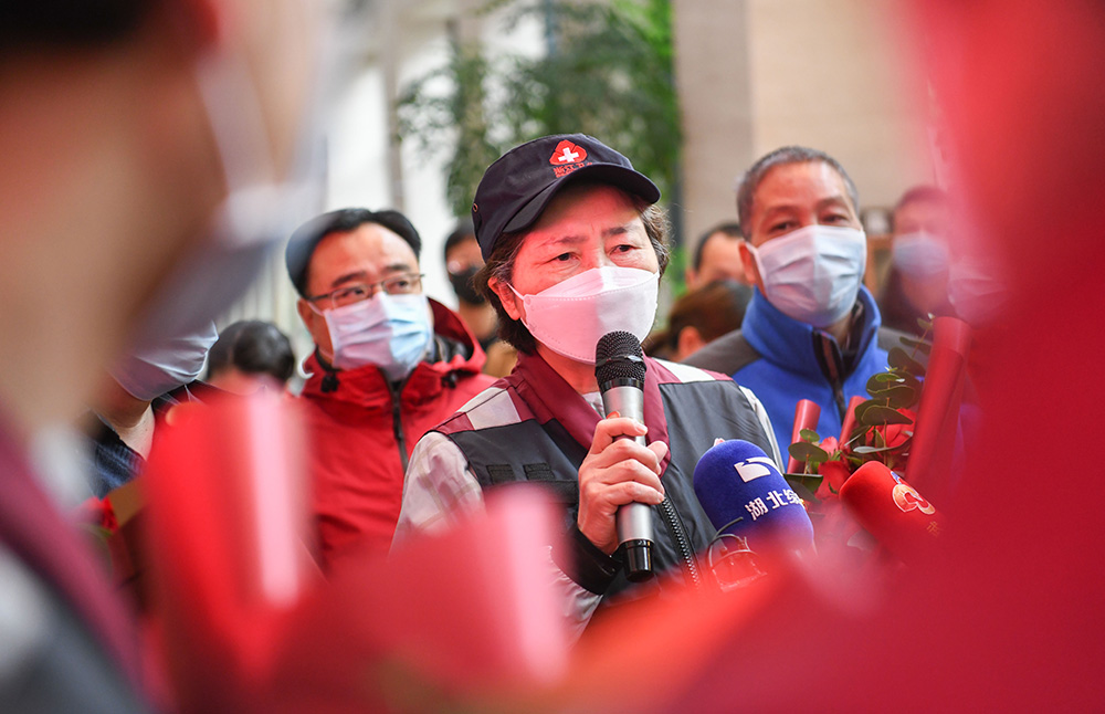 Li Lanjuan wearing a white face mask and baseball cap                speaking to a crowd through a microphone.