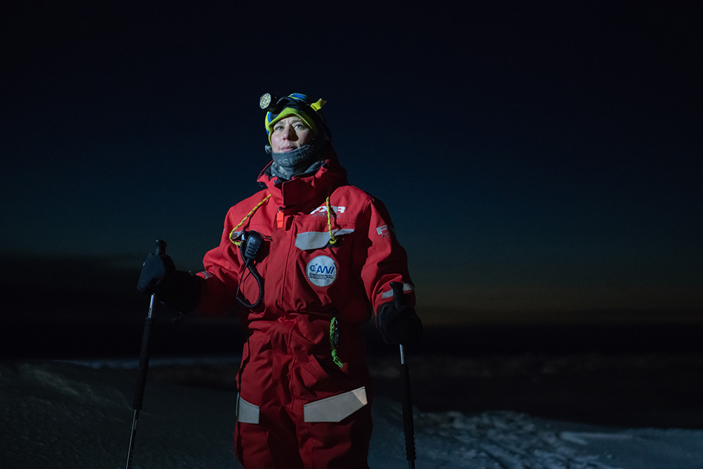 Verena Mohaupt photographed wearing red cold weather                gear, skis and holding ski poles on an ice floe during                Arctic night.