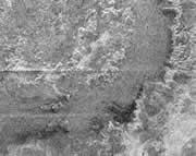 Cassini's views of Titan show craters and scratches. Click here for more pictures  type='special.