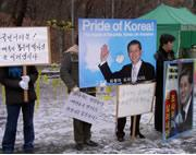 Protestors stand outside the university, standing by Hwang and asking for more time for him to prove his methods.