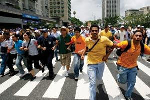 Cutbacks have sparked protests in Caracas against President Hugo Ch&x00E1;vez (inset).