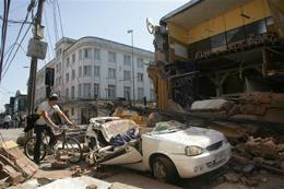 A man rides his bicycle along a destroyed building in Concepcion,  Chile, Saturday Feb. 27, 2010 after an 8.8-magnitude struck central  Chile.