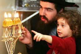 Boy watching his father lighting Menorah on last day of Chanukah.