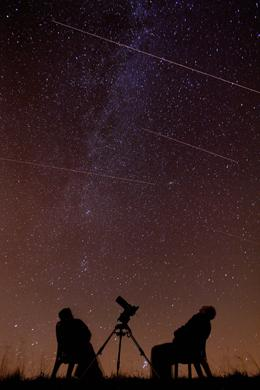 Astronomers Mark and Denise Gibbons watch as meteors from the Perseid meteor shower streak through the sky at 2.00am over Stroud, Gloucestershire, UK, August 13 2007