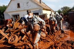 Hungarian soldiers clean a yard flooded by toxic mud in Devecser, Hungary, Thursday, Oct. 7, 2010.