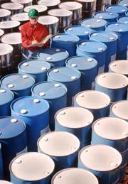 Worker inspecting rows of chemical drums