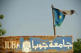 A tattered Southern Sudan flag flutters in the wind over a rusted sign reading 'Juba University' on January 10, 2011.