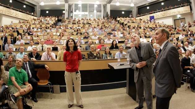 A rapt crowd watches as physicists Fabiola Gianotti       (standing, left), Rolf Dieter-Heuer (right) and Joe Incandela (far       right) unveil evidence for the Higgs boson.