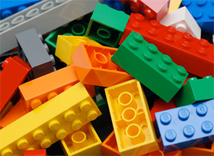 a close up photograph shows a pile of multicolored lego building blocks